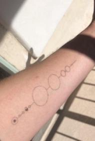 男生手臂上黑色的圆形极简线条纹身图案